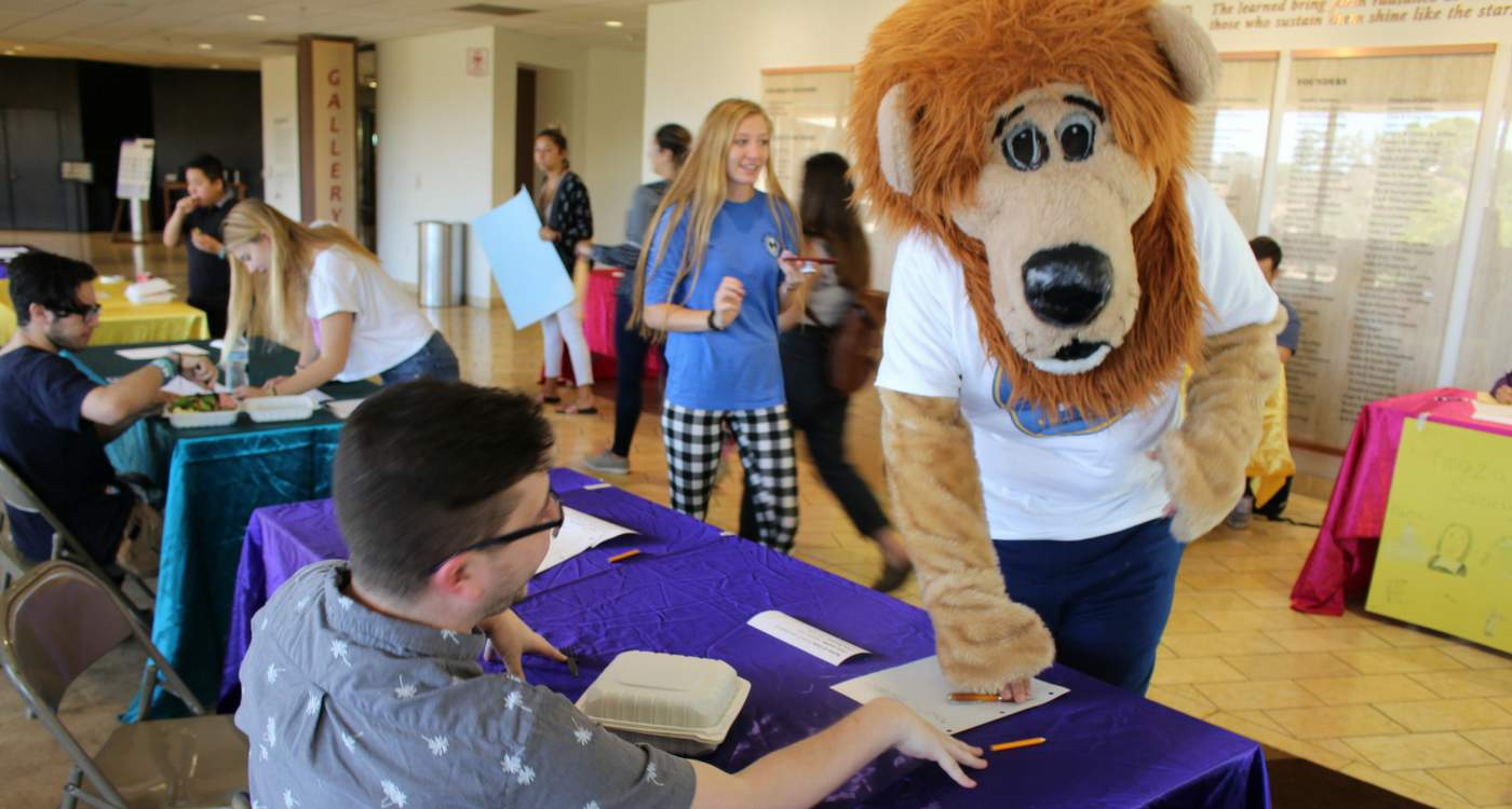 Photograph of AJU mascot Zion the lion greeting students