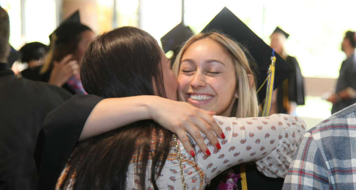 Photo of two people hugging at graduation ceremony