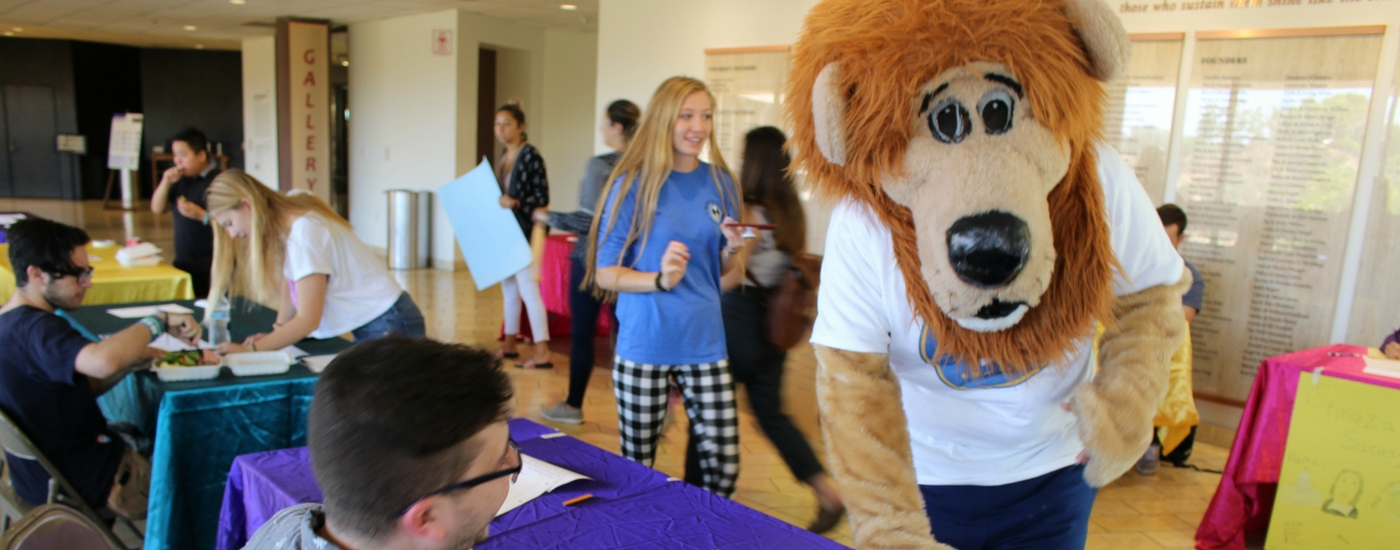 Photograph of mascot, Zion the lion with students