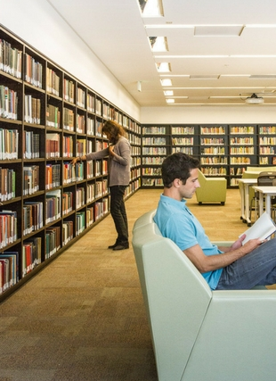 Photograph of two students in the library at the stacks