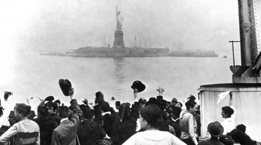Photograph of immigrants near the statue of liberty (black and white)