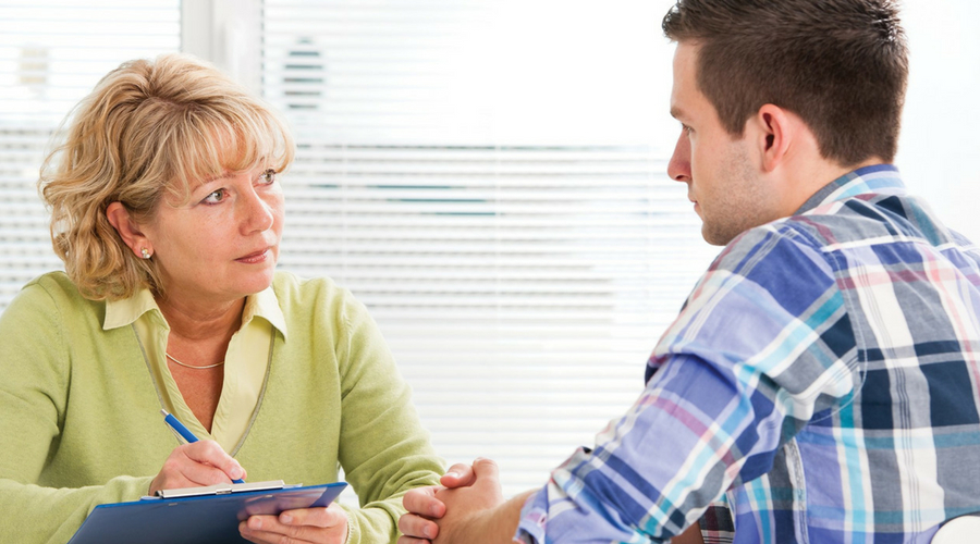 Image of woman listening to man talking in therapy-like session