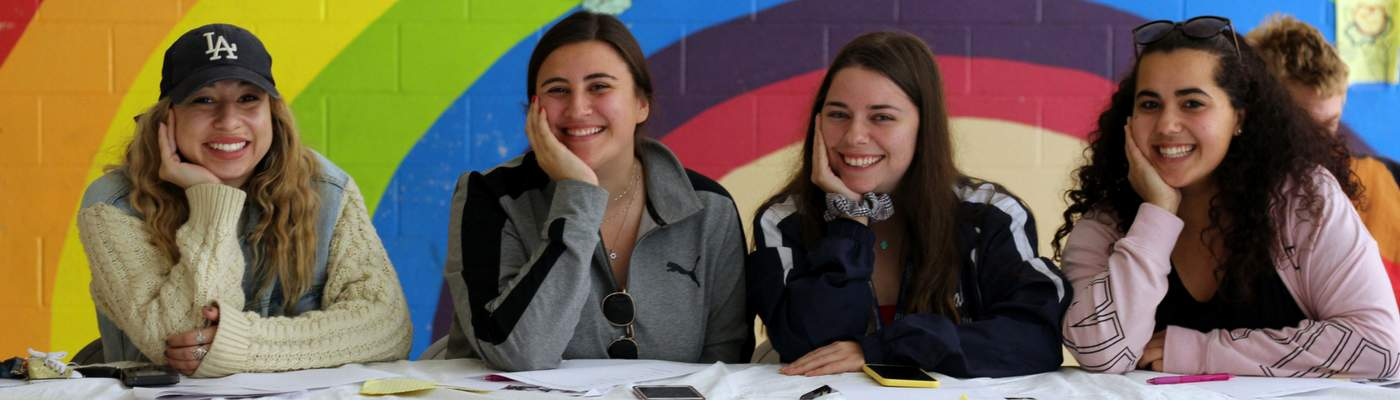 Photograph of 4 female students with rainbow painting in the background.