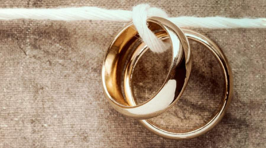 Image of two wedding rings tied with string to represent marriage for life.
