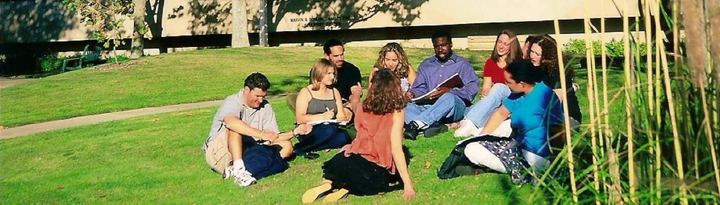 Photograph of students sitting on grass in sculpture garden