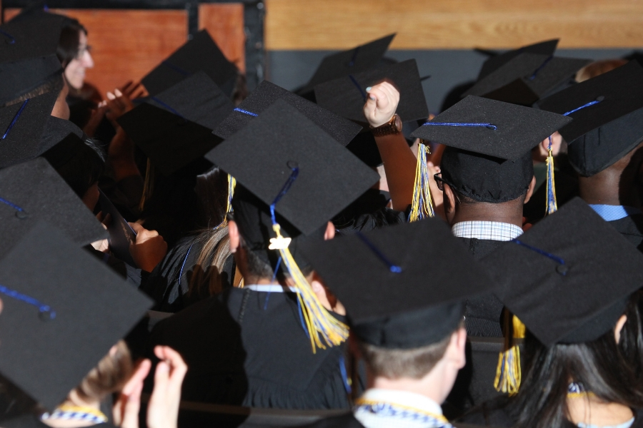 Photograph of the back of graduates in caps and gowns