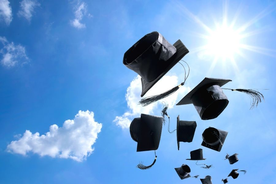 Image of graduation caps thrown up in the air