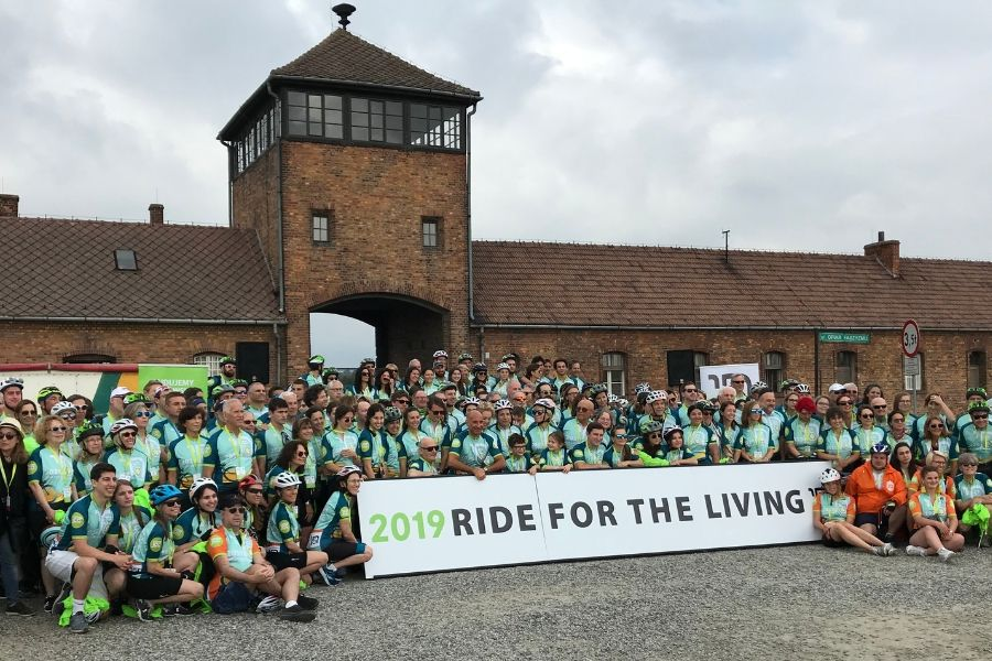 Photograph of cyclists in front of concentration camp for Ride for the Living