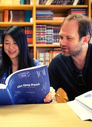 Photo of two students studying from book