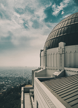 View of downtown Los Angeles skyline at horizon, with Griffith Observatory in foreground.