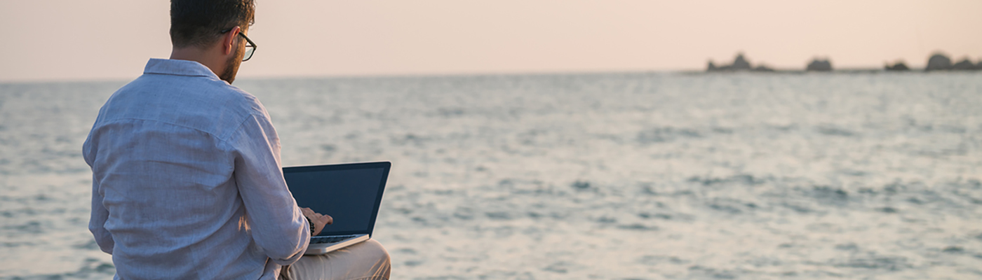 Youn man working on laptop on beach during early morning, with ocean horizon in background.