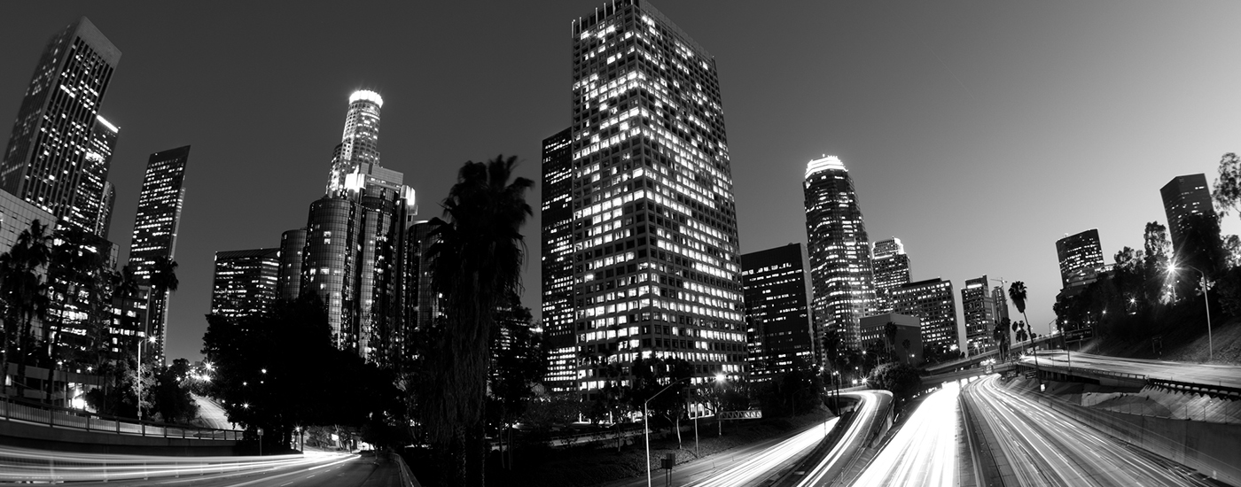 Black and white timelapse photograph of downtown Los Angeles skyscrapers and freeway traffic at night.