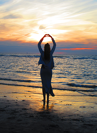 Barefoot young woman on beach, standing at water line, facing the setting sun, and raising her hands in the shape of a heart.