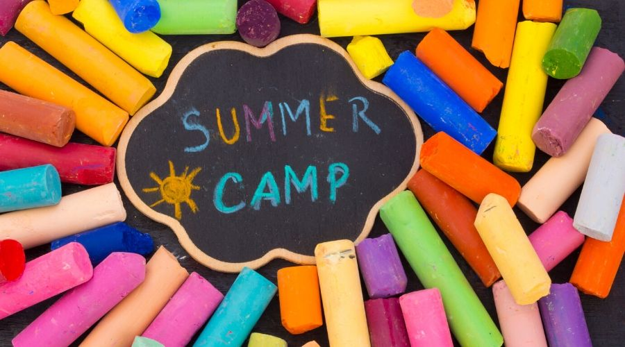 a pile of multicolored chalk that spells out Summer Camp