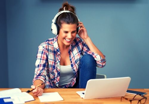 woman wearing headphones on computer