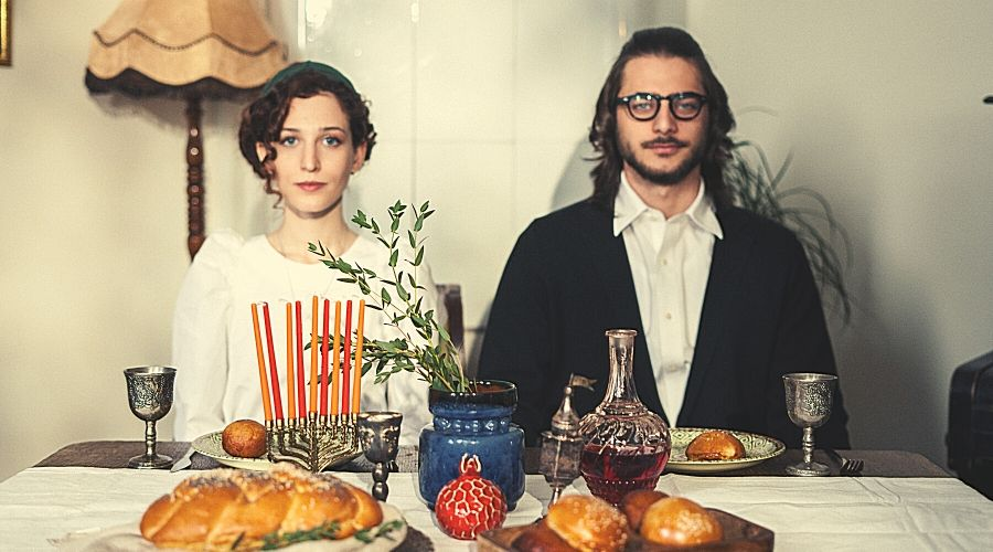 an ultra-orthodox couple sitting at their shabbat table